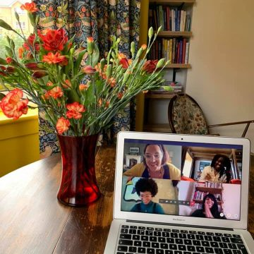 On top of a kitchen table are a vase of flowers and a laptop screen showing an online workshop with Hannah Lavery, Jess Brough, Alycia Pirmohamed and Celementine Burnley