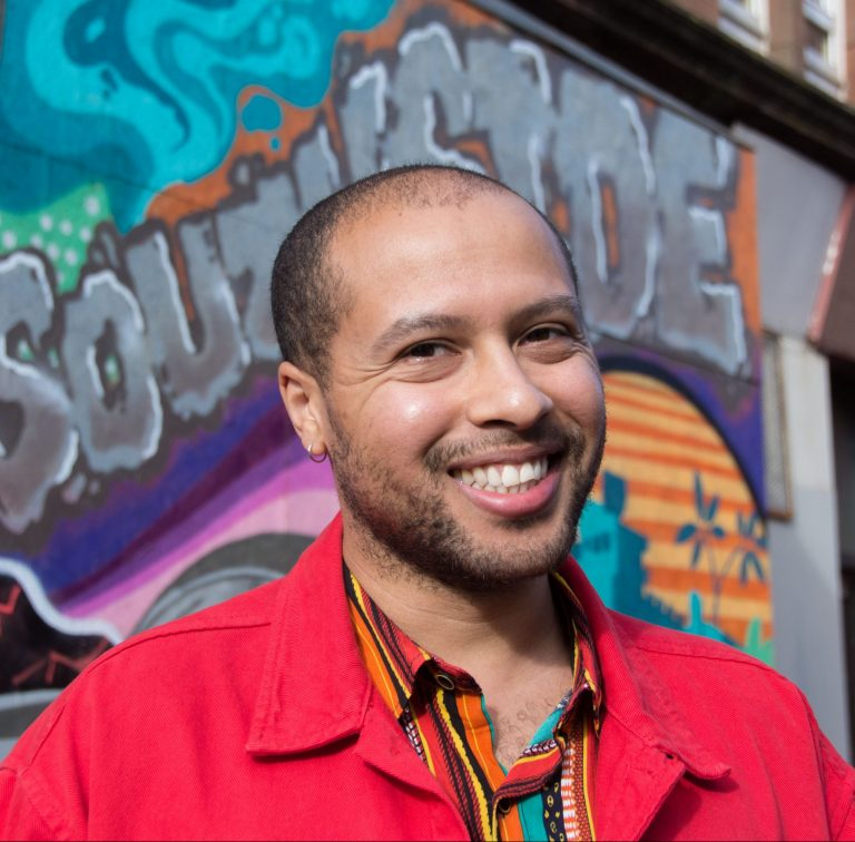 """A mixed-race man of light brown complexion smiles directly at the camera. He is in his early thirties. He has stubble and short cropped hair. He's wearing a multicoloured shirt and a bright red jacket. Behind him is a wall of colourful graffiti with the word """"SOUTHSIDE"""" partially obscured by his head but still just about legible."""