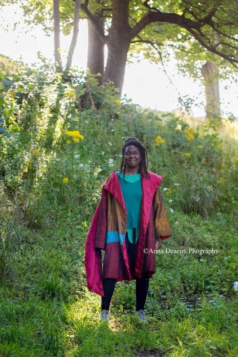 Black woman in purple and blue clothing stands surrounded by greenery and trees