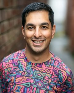 A photo of Sanjay Lago he wears a colourful patterened shirt and has black hair and brown skin. He smiles at the camera.