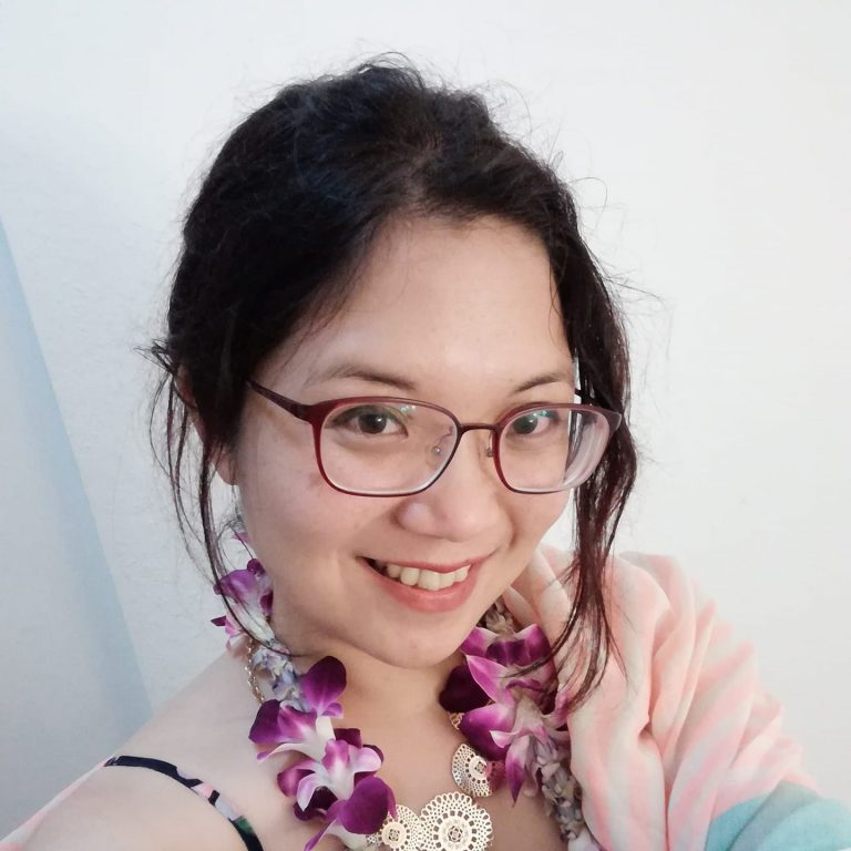 Kelly is smiling at the camera. She is an East Asian and Southeast Asian woman with glasses and black hair.