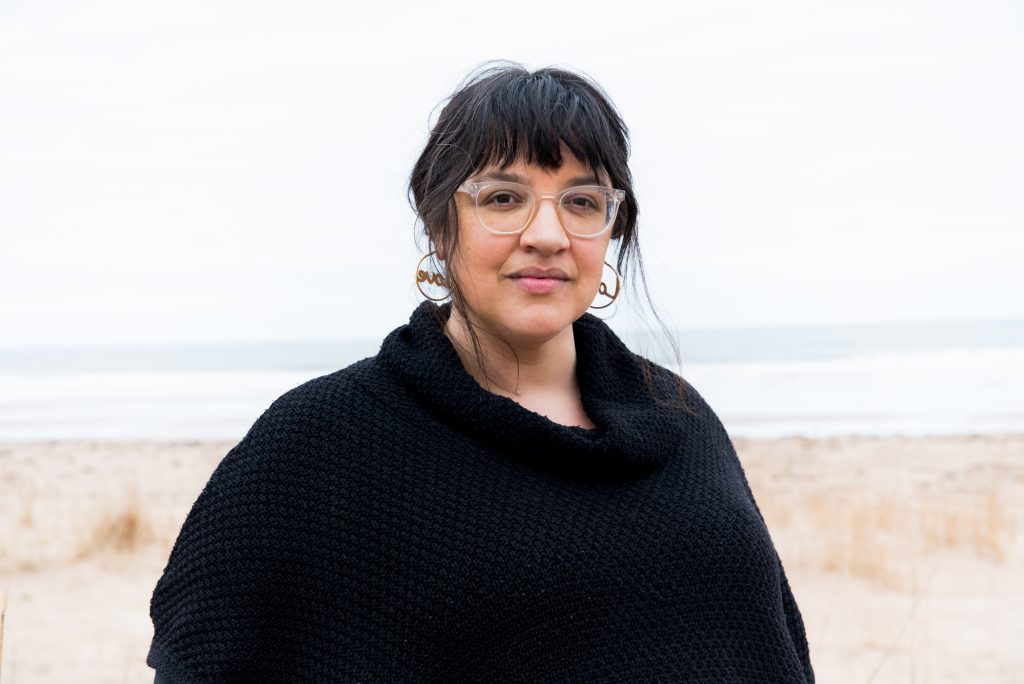Photo of a woman wearing clear-rimmed glasses, circular earrings and a black coat. She has black hair with a fringe and light brown skin and in the background is a sandy beach and shoreline.