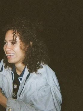Photo of Eilidh Akilade - a Black woman with curly hair and a jacket, smiling