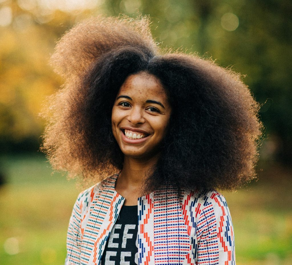 Titilayo smiles at the camera. They are a lightskinned Black person and are standing in a park, wearing a patterned jacket. Titi wears their hair in a big afro which is swaying in the wind.