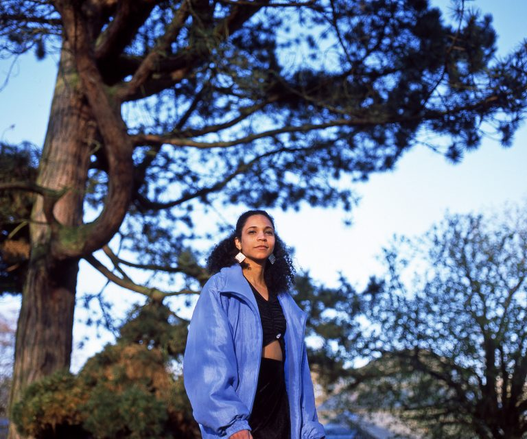 A Black woman with long hair and a blue jacket standing under a tree.