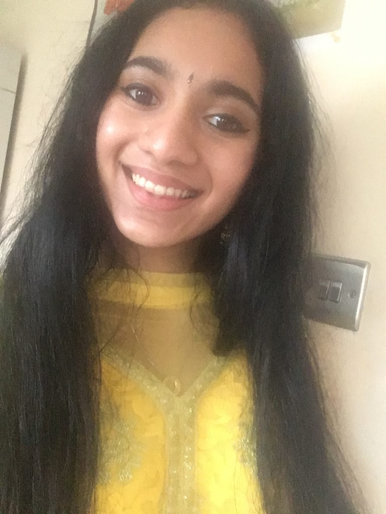 An Indian-Scottish woman with long hair, smiling.