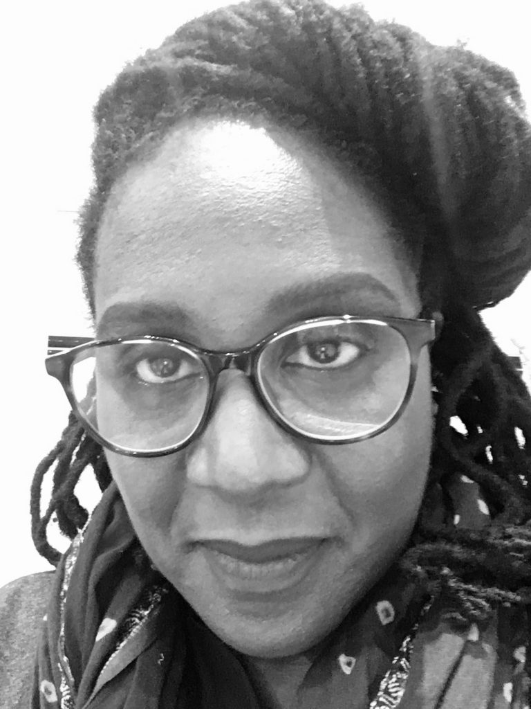 A black and white photo of a Black woman with glasses and dreadlocks looking at the camera.