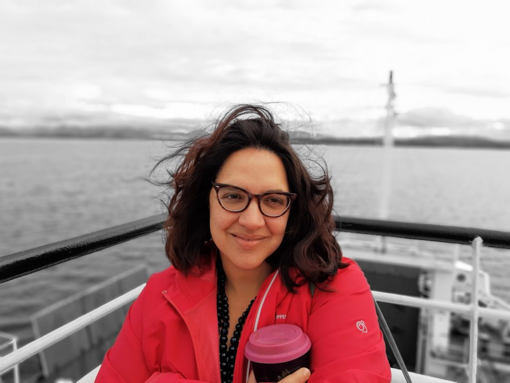 A Black woman on a boat, with shoulder-length hair & glasses, looking slightly off-camera.