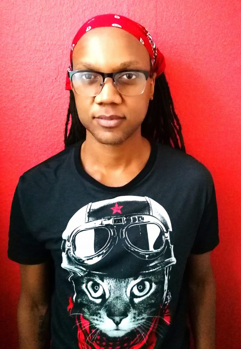 A Black man with glasses, a black T-shirt with a cat in a pilot's helmet, and long dreadlocks tied back by a red bandanna, looking at the camera.