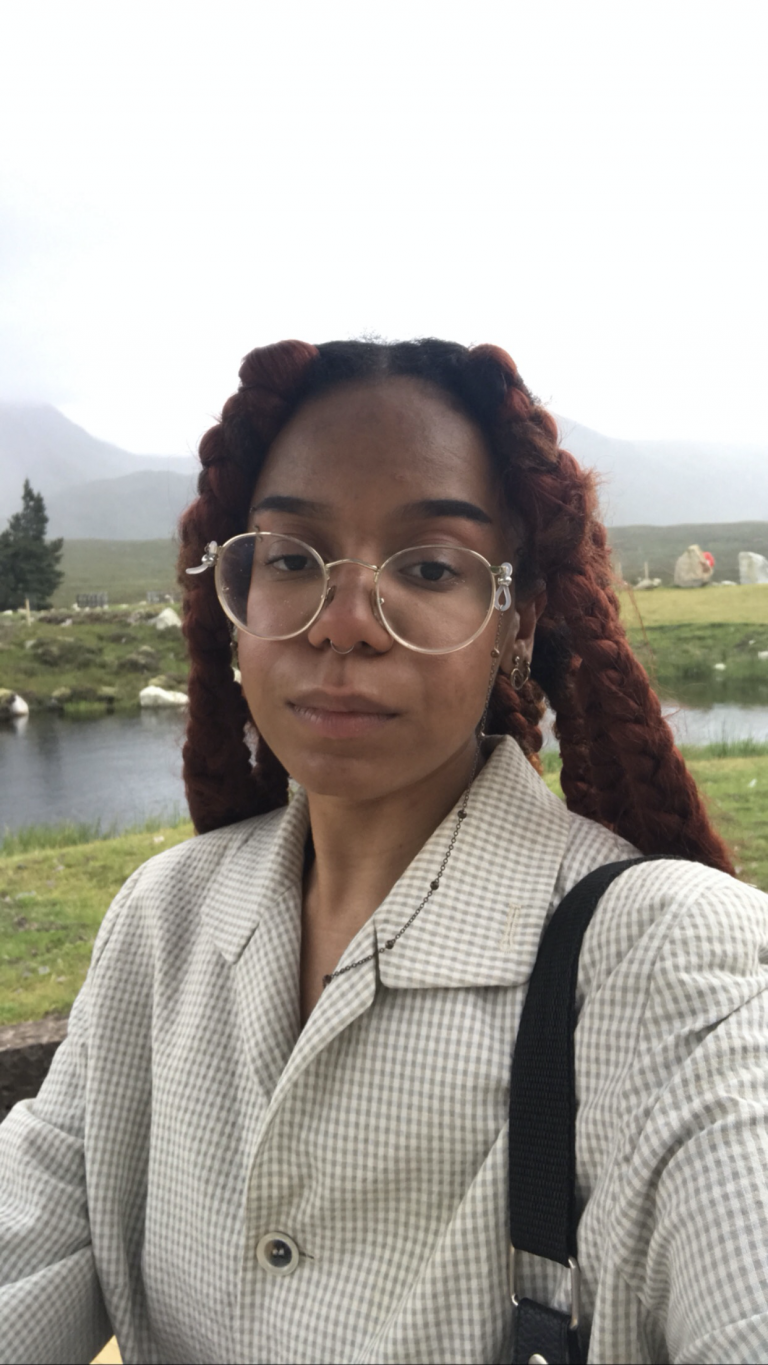 A Black person with long braids, glasses, and a beige coat looking at the camera.