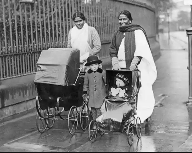 Old black and white photo of two Indian woman pushing prams, with a child in a hat and coat standing near one pram.