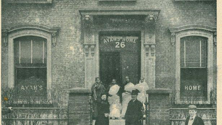 Black and white photo of four Indian women, a white woman, and a police officer standing outside the door of a building.