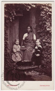 Sepia photo of an Indian woman sitting with two white children.